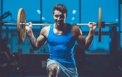Красивая модельная разминка молодого человека в спортзале Стоковые Фотографии RF