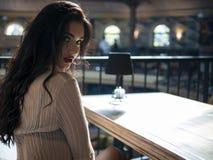 Красивая модель брюнета сидя на кресле на таблице внутри помещения по стоковые фото