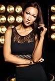 Красивая модель девушки в черных одеждах представляя на черной студии освещает предпосылку Стоковое Изображение RF
