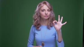 Красивая модель с волнистыми длинными волосами показывая в порядке жест на зеленой предпосылке chroma акции видеоматериалы