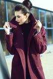 Красивая модель с идеальным составляет и волосы сдаватьые в утиль назад в плюшку держа хлопнутый вверх воротник ее maroon пальто стоковая фотография