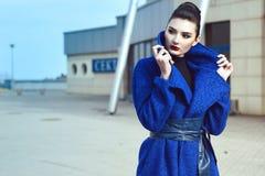 Красивая модель с идеальным составляет и волосы сдаватьые в утиль назад в положение плюшки на улице в голубом пальто с кожаным по стоковое изображение