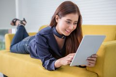 Красивая молодая азиатская женщина используя цифровой планшет лежа на желтой софе дома в живущей комнате стоковое изображение rf