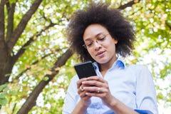 Красивая молодая африканская женщина используя телефон в природе стоковое фото rf