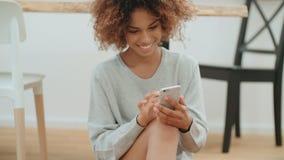 Красивая молодая афро американская женщина используя мобильный телефон дома видеоматериал