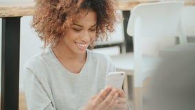 Красивая молодая афро американская женщина используя мобильный телефон дома акции видеоматериалы