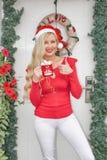 Красивая молодая белокурая девушка в крышке Санта стоит на парадном входе украшенном с венком и ветвями спруса стоковые фото
