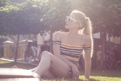 Красивая молодая белокурая девушка ослабляет на траве в парке города, Central Park на солнечный день Стоковые Фото