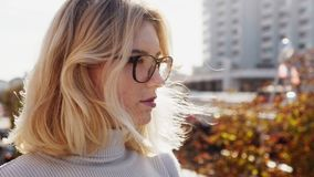 Красивая молодая белокурая женщина при стекла смотря прочь на солнечном городе осени видеоматериал