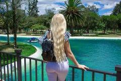 Красивая молодая белокурая женщина стоя с ей назад на мосте и смотря красивый ландшафт, пруд и обозревать PA стоковое фото rf