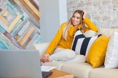 Красивая молодая белокурая студентка используя портативный портативный компьютер пока сидящ в винтажной кофейне Молодые Стоковые Фотографии RF