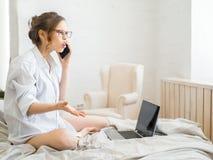 Красивая молодая беременная женщина сидя на кровати используя приборы технологии: компьтер-книжка и телефон в современной комнате стоковое фото