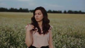 Красивая молодая беспечальная девушка с длинным вьющиеся волосы над предпосылкой ландшафта пшеничного поля цветка Блески солнца з сток-видео