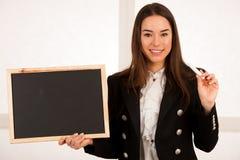 Красивая молодая бизнес-леди держа пустой изолят классн классного Стоковое Изображение RF