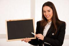Красивая молодая бизнес-леди держа пустой изолят классн классного Стоковое фото RF
