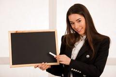 Красивая молодая бизнес-леди держа пустой изолят классн классного Стоковые Изображения