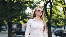 Красивая молодая бизнес-леди с солнечными очками идет через город пешком Смотреть на окраинах города акции видеоматериалы