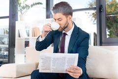 красивая молодая газета чтения бизнесмена и выпивая кофе Стоковые Фотографии RF