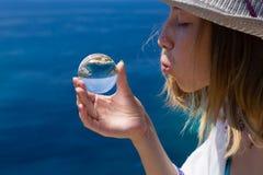 Красивая молодая дама с стеклянным шариком Сторона, рука, естественная сцена outdoors как обои моря предпосылки голубые слишком п стоковое фото