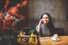 Красивая молодая девушка брюнет говоря на мобильном телефоне на деревянном столе около окна и выпивая кофе в украшенном кафе стоковая фотография rf