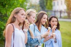 Красивая молодая девушка студента есть мороженое в парке стоковые фотографии rf