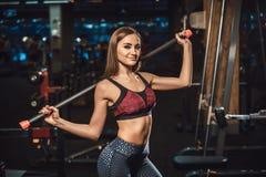 Красивая молодая девушка фитнеса представляя с оборудованием спорта в спортзале смотря камеру представлять с штангой Стоковая Фотография RF