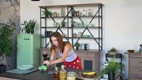 Красивая молодая домохозяйка обтирая таблицу с полотенцем и поднимаясь вверх по бокалу вина в кухне во время сконцентрированного  сток-видео