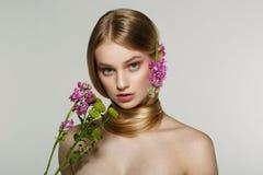 Красивая молодая женская модель с голубыми глазами, идеальная кожа с цветками на плече стоковые фото