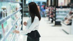 Красивая молодая женщина выбирает косметики в магазине, кладет ее в корзину акции видеоматериалы