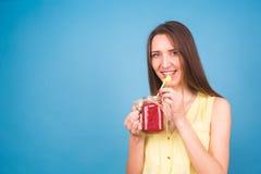 Красивая молодая женщина выпивает smoothie клубники на голубой предпосылке Здоровая органическая концепция пить Люди на диете Стоковое Изображение RF