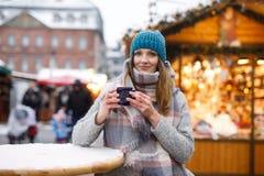 Красивая молодая женщина выпивая горячий пунш, обдумыванное вино на немецкой рождественской ярмарке Счастливая девушка в одеждах  стоковое изображение rf
