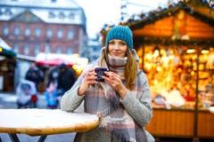 Красивая молодая женщина выпивая горячий пунш, обдумыванное вино на немецкой рождественской ярмарке Счастливая девушка в одеждах  стоковые изображения