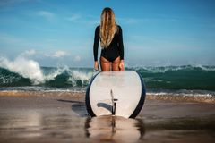 Красивая молодая женщина в бикини с доской прибоя на пляже тропического острова Стоковые Фотографии RF