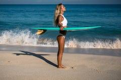 Красивая молодая женщина в бикини с доской прибоя на пляже тропического острова Стоковые Фото