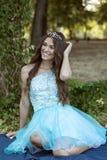 Красивая молодая женщина в голубом платье представляя с кроной на ей стоковая фотография rf