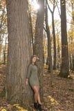 Красивая молодая женщина в зеленых представлениях платья в древесины осени стоковая фотография