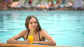 Красивая молодая женщина в лете Девушка бикини ослабляя в тропическом бассейне женщина выпивая свежий апельсин видеоматериал