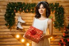 Красивая молодая женщина в оформлении Нового Года с подарком, концепцией праздников Нового Года стоковые фотографии rf
