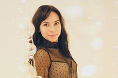 Красивая молодая женщина в платье коктейля оставаясь усмехающся над предпосылкой светов стоковое изображение