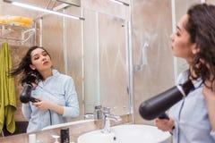 Красивая молодая женщина в полотенце ванны использует фен для волос и смотрит в зеркало стоковое изображение rf