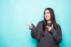 Красивая молодая женщина в свитере указывая сторона и усмехаясь на предпосылке бирюзы стоковые фото