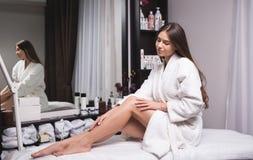 Красивая молодая женщина в современном салоне красоты показывая ей совершенные тонкие ноги стоковое изображение