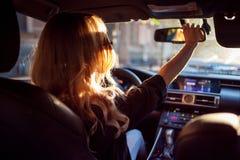 Красивая молодая женщина в солнечных очках сидя за колесом автомобиля и исправляет зеркало Фото от заднего сиденья Стоковое Изображение
