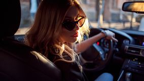 Красивая молодая женщина в солнечных очках сидя за колесом автомобиля Фото от заднего сиденья Стоковая Фотография
