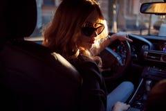 Красивая молодая женщина в солнечных очках сидя за колесом автомобиля Фото от заднего сиденья Стоковые Фото