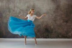 Красивая молодая женщина в сочной голубой юбке, завихряясь и танцуя стоковое изображение