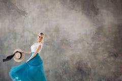 Красивая молодая женщина в сочной голубой юбке, завихряясь и танцуя Стиль лета, соломенная шляпа с черной лентой стоковое изображение rf