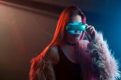 Красивая молодая женщина в футуристической виртуальной реальности стекел, стиле киберпанка, неоновом свете Стоковое фото RF