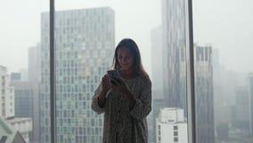 Красивая молодая женщина готовит телефон польз окна умный на предпосылке городского города во время дождя 3840x2160 акции видеоматериалы