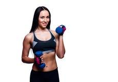 Красивая молодая женщина делает тренировки с гантелями в студии Sporty атлетическая девушка поднимаясь вверх по весам против бело Стоковое фото RF